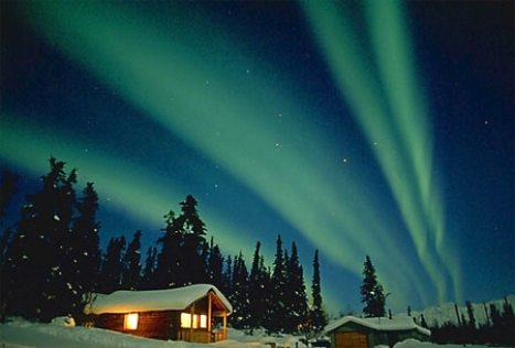 Aurora lights up sky over log cabin